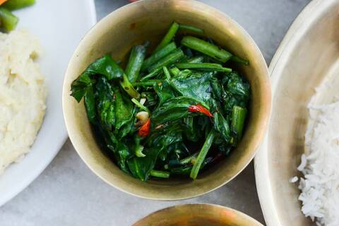 Deatils of one of the bronze bowls with Saag (Nepali spinach)
